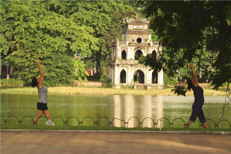 Local people do exercises around Hoan Kiem Lake